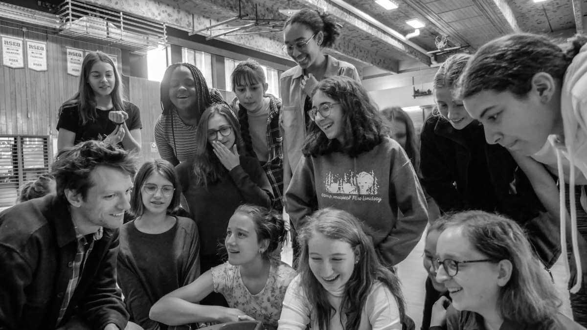 Alexis Raynault, maître d'oeuvre du Vaisseau-cœur, en compagnie des jeunes choristes de l'école Joseph-François Perreault. (Photo: Charlie Poirier-Bouthillette)