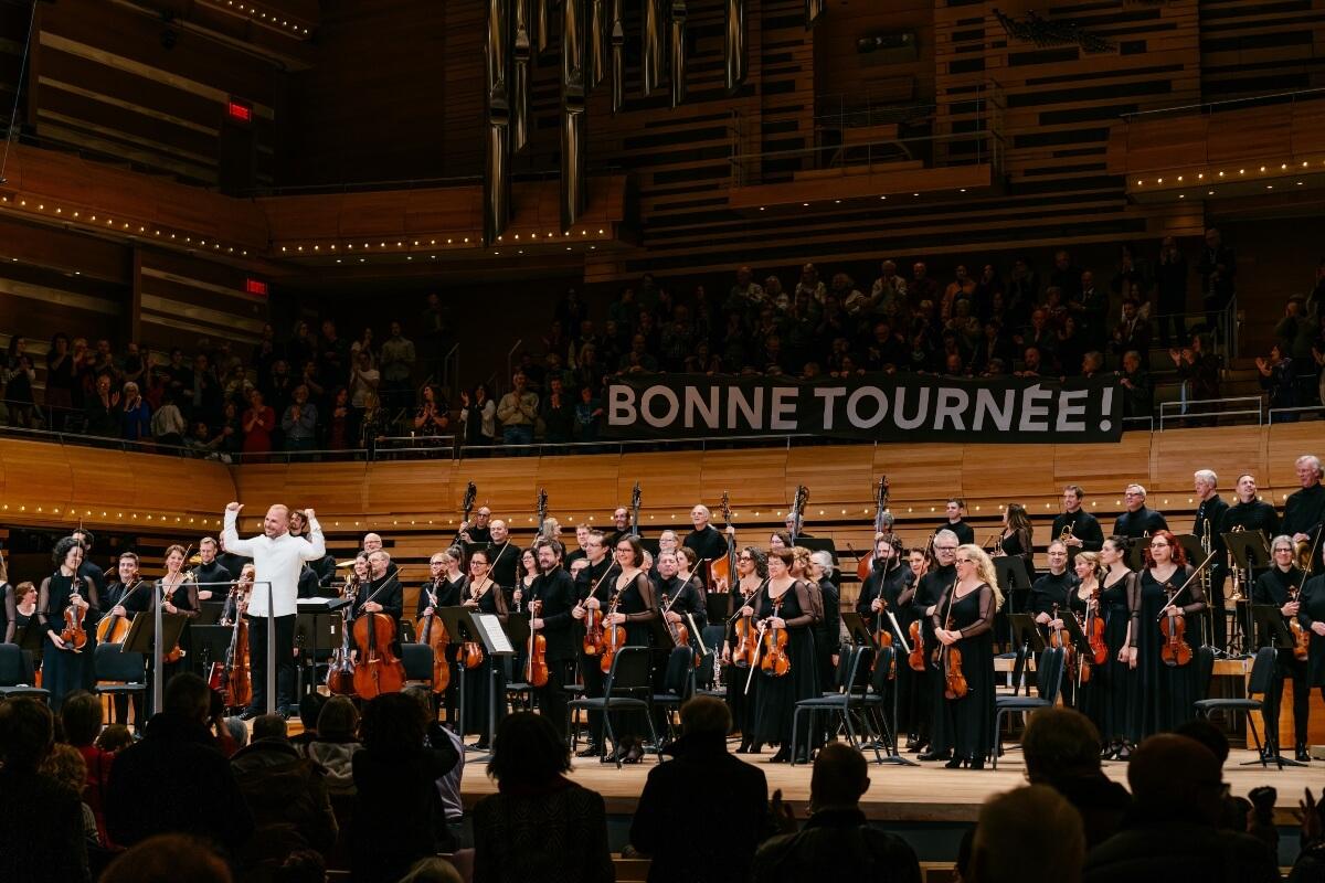 """Orchestre Métropolitain et Yannick Nézet-Séguin sur la scène de la Maison symphonique, avec une banderole """"Bonne tournée"""", 17 novembre 2019 (Photo : François Goupil)"""