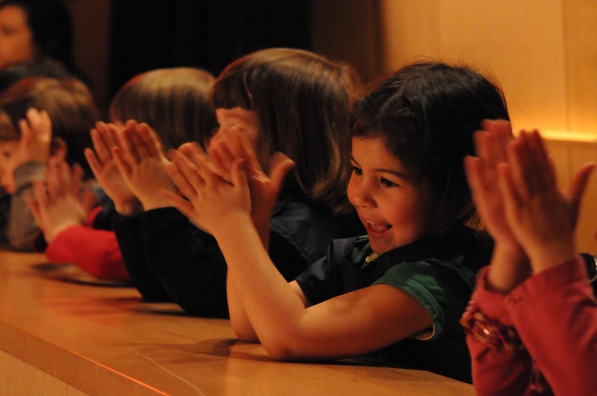 enfants applaudissant à un concert des Jeunesses musicales