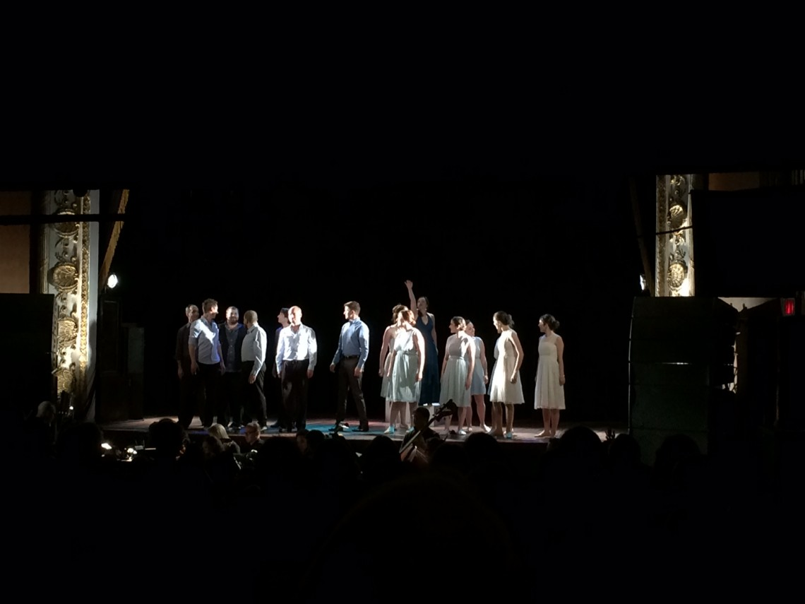 Soprano Jacqueline Woodley (with arm raised) is surrounded by the 14-member chorus in Against the Grain Theatre's Messiah at the Opera House on Saturday night (John Terauds iPhone photo).