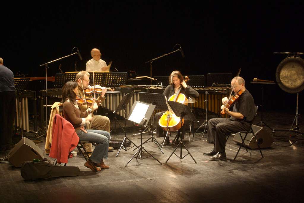 Steve Reich Ensemble playing Different Trains (from left to right) Liz Lim-Dutton, violin, Todd Reynolds, violin, Jeanne LeBlanc, cello, Scott Rawls, viola, Russ Hartenberger at the back (Photo: Flickr.com)