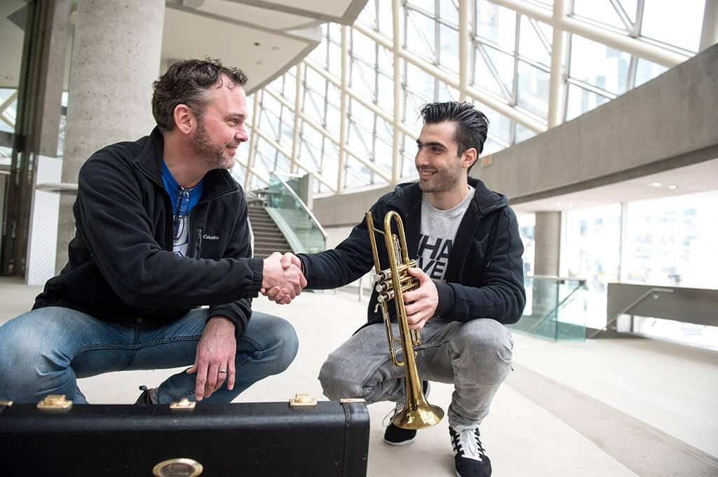 TSO Principal Trumpet Andrew McCandless donates a replacement Trumpet to Syrian musician Abdo Elias (Photo: Jag Gundu)