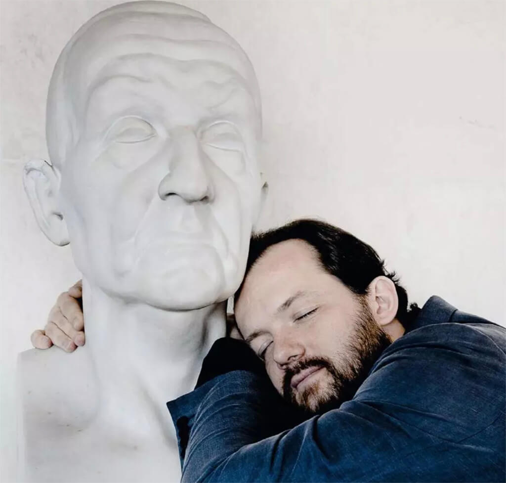 Andris Nelsons, takes a nap with a bust of Anton Bruckner. (Photo: Marco Borggreve)