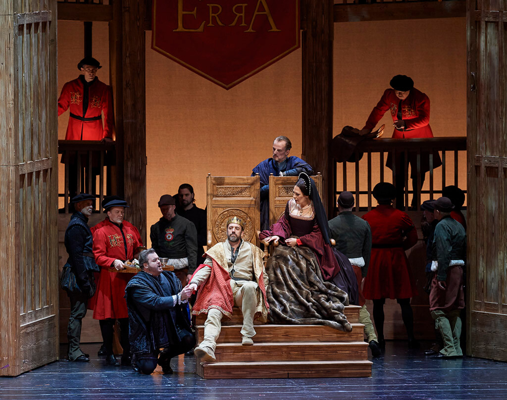 (l-r) Bruce Sledge as Riccardo Percy (kneeling), Christian Van Horn as Enrico VIII, Thomas Goerz as Lord Rocheford (behind chair) and Sondra Radvanovsky as Anna Bolena in the Canadian Opera Company's production of Anna Bolena, 2018. (Photo: Michael Cooper)