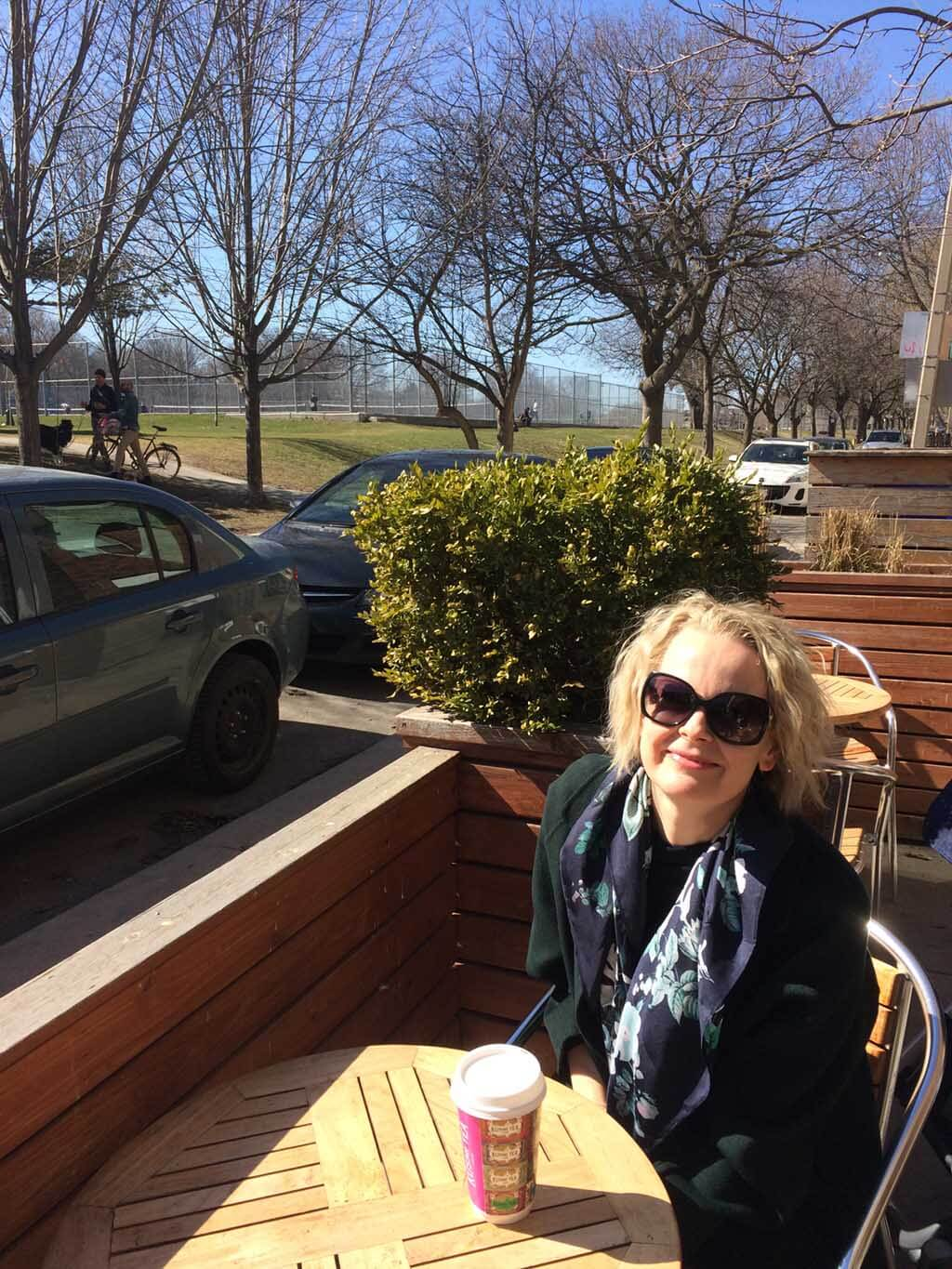 Carla Huhtanen enjoys a coffee with Trinity Bellwoods Park tennis courts in background