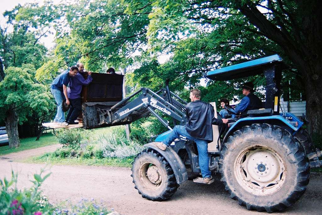 Michael Schmidt loads a piano with a tractor (Photo courtesy of Symphony In The Barn)