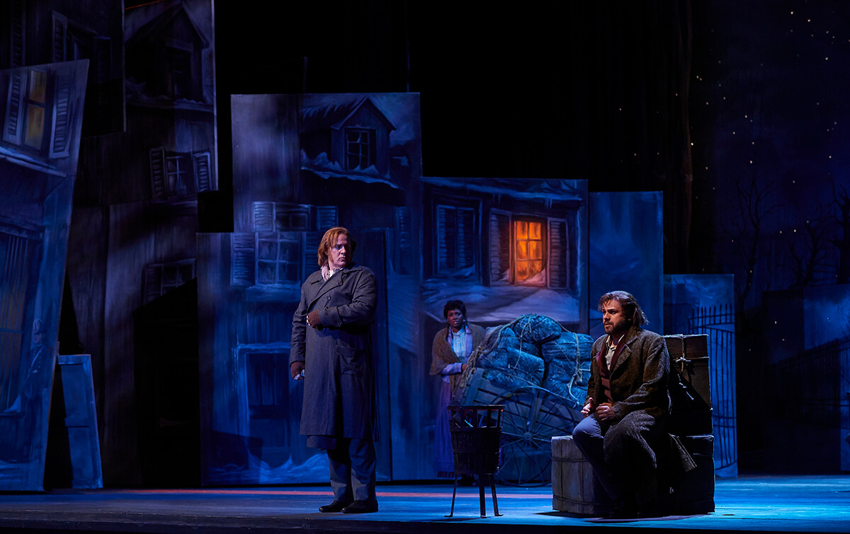 (l-r) Lucas Meachem as Marcello, Angel Blue as Mimì (in background), and Atalla Ayan as Rodolfo in the Canadian Opera Company's production of La Bohème, 2019. (Photo: Michael Cooper)