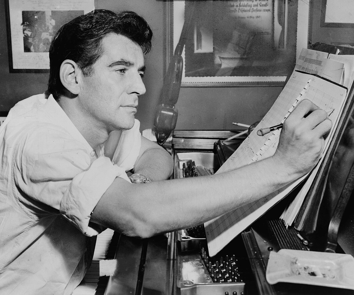 Leonard Bernstein seated at piano, making annotations to musical score, 1955 (Public domain photo from the Library of Congress, New York World-Telegram & Sun Collection)
